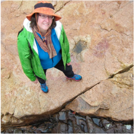 Michele in colorful rain outfit on an outcrop