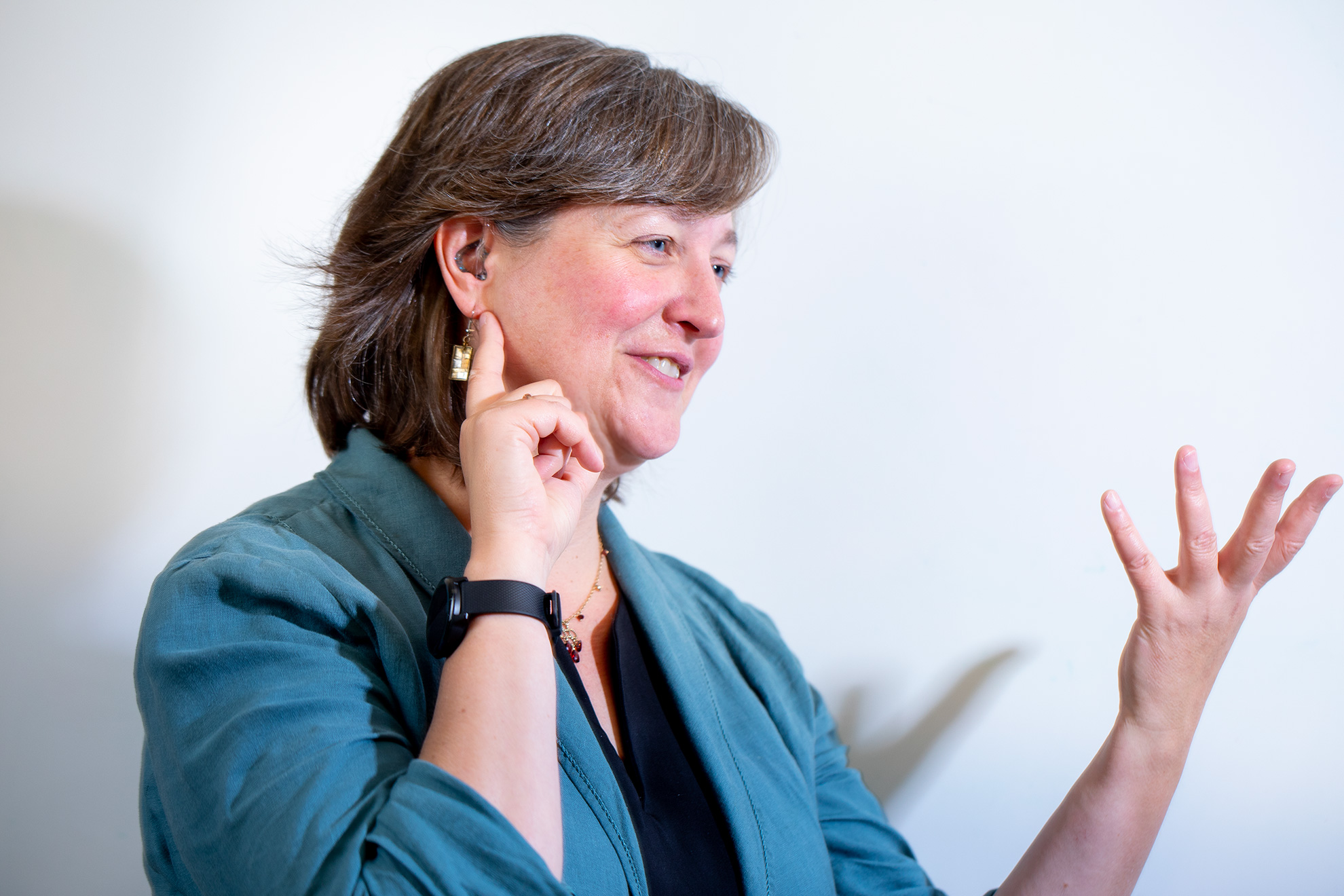 Woman gesturing and wearing behind the ear hearing aids