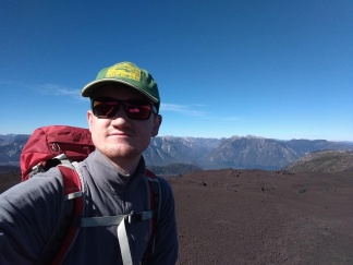 white man in bright sunshine (hat and sunglasses) on a rocky volcano barren of vegetation