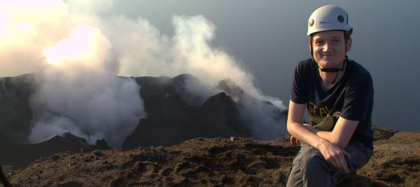 white young man with helmet on Stromboli volcano with gas steam in background and rocky landscape
