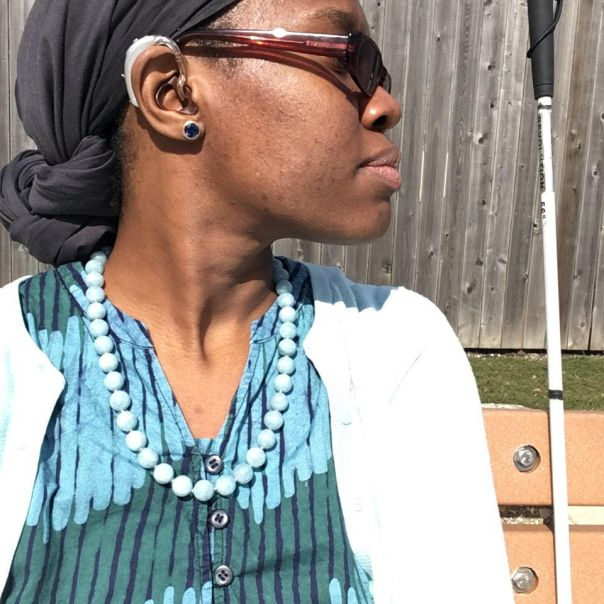 A brown-skinned woman wearing a blue patterned dress, a gray headwrap, and hearing aids sits on a bench looking to the right. To her right, a white cane stands upright.