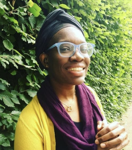 A dark skinned woman with glasses and head scarf smiles to the camera