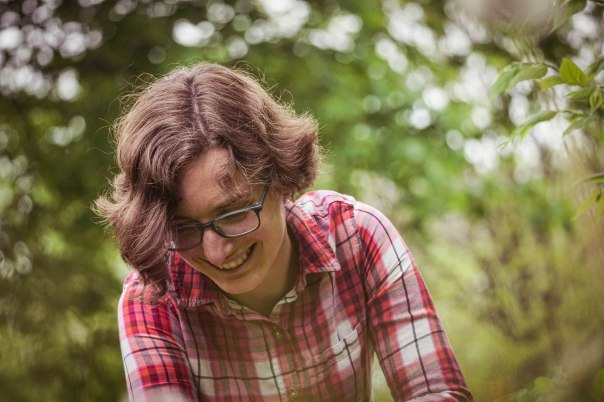 Pale skinned woman with short wavy brown hair and plaid shirt laughs while looking downward