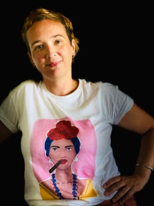 A white woman with light brown short hair smiles with her hand on her hip. She is wearing a white t-shirt with an image of Frida Kahlo.