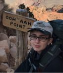 "Young white woman sites with a canyon behind her. She wears a baseball hat and glasses. The wooden  sign next to her says ""Ooh Aah Point""."