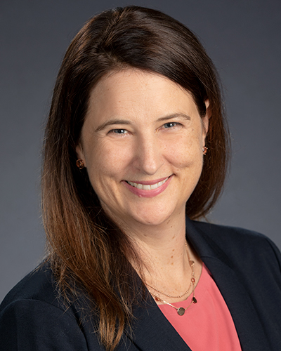 A smiling white woman with straight, shoulder length brown hair. She is wearing a pink top and dark blazer, and a delicate chain around her neck.