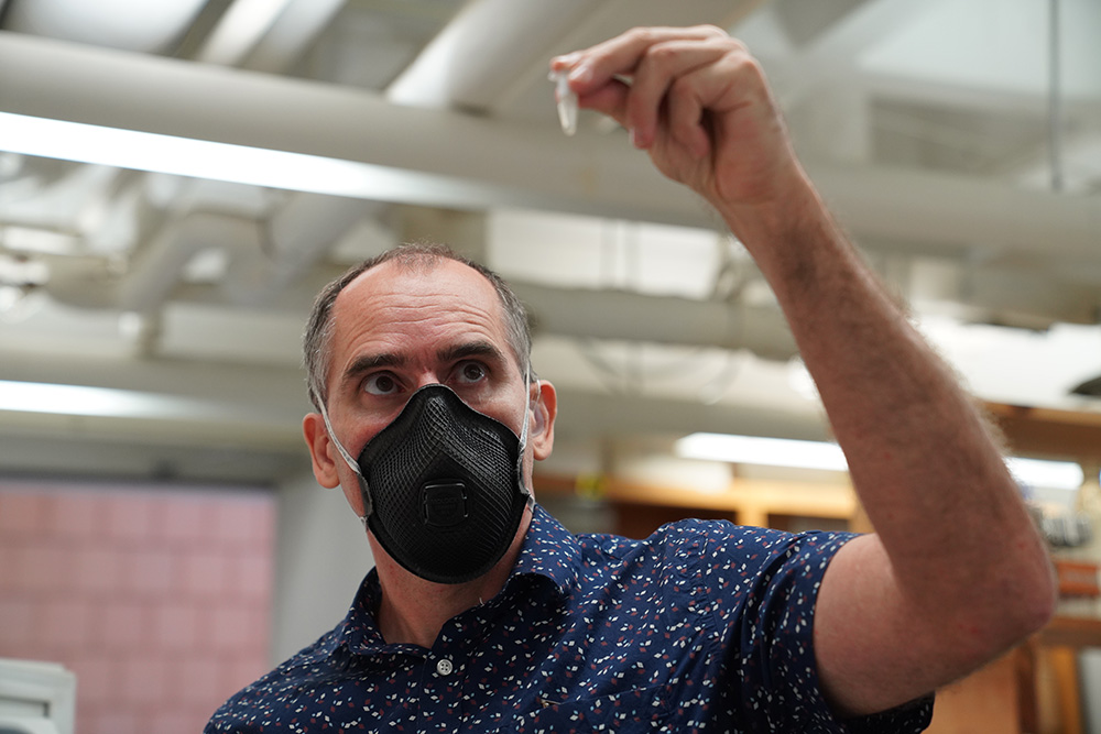 A white man with grey hair and a mask covering mouth and nose holds an eppendorf test tube and eyes its contents. He is wearing a dark blue shirt with a pattern and is in a laboratory type setting with white pipes in the background.