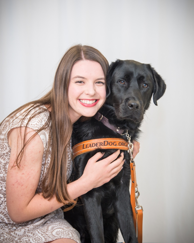 A white woman with a big smiling face pressed to her guide dog's face, they are both sitting and her arm is wrapped around him. She has straight long brown hair and is wearing a white and tan dress, and he is a black lab wearing a leather harness that says leaderdog.org.